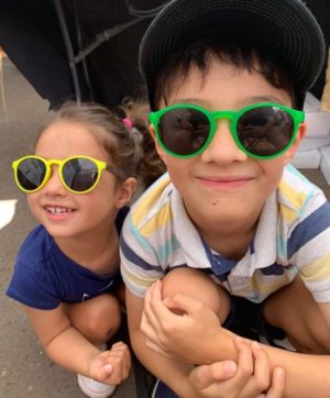 boy and girl wearing yellow wooden sunglasses